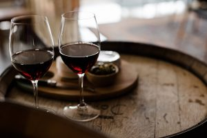 Close of up two red wine glasses on a barrel