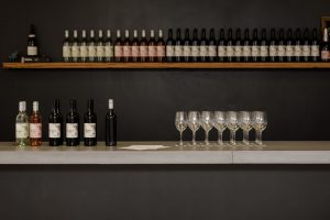 A wide shot of a bar full of wine bottles and glasses