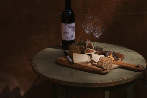 A cheese board with two empty glasses of wine